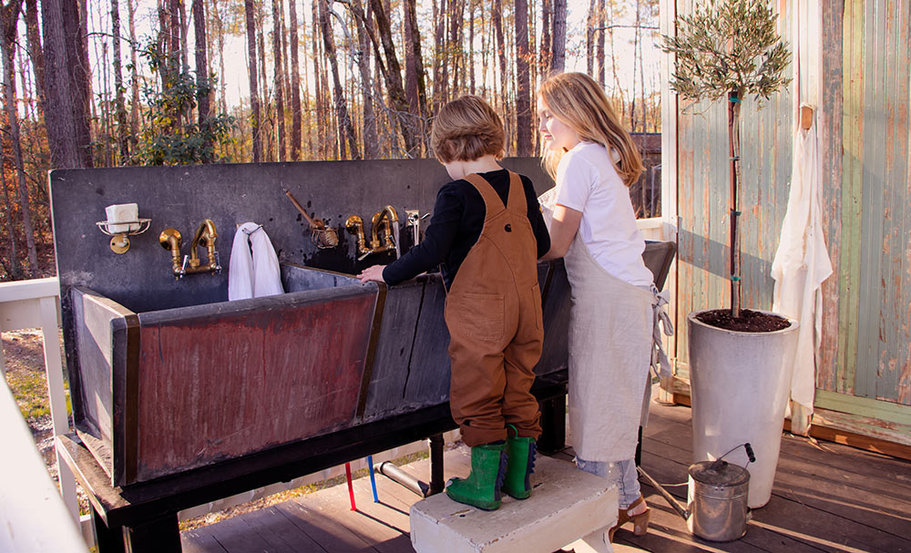 A  young boy and girl washing with antique sinks.